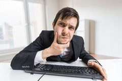 Suspicious man is working with computer and looking on screen Royalty Free Stock Image