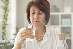 Suspicious middle age woman looking glass of water Stock Photography