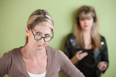 Suspicious Mom. Daughter with on headphones behind suspicious mom Royalty Free Stock Image