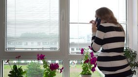 Suspicious pregnant woman calling police on phone while looking through window
