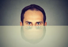 Suspicious scared man peeking from under the table hiding Stock Images