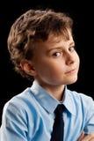 Suspicious schoolboy. Portrait of a suspicious schoolboy isolated on black background Royalty Free Stock Image