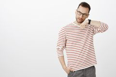 Suspicious serious handsome male model in glasses, holding hand near ear and listening to watch, standing over gray wall. Checking if device working corectly Royalty Free Stock Photography