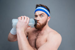 Suspicious shirtless sportsman drinking water and looking at camera Royalty Free Stock Photo