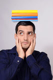 Suspicious student holding a pile of books on his head raising his eyebrow. Royalty Free Stock Images