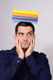 Suspicious student holding a pile of books on his head raising his eyebrow. Royalty Free Stock Image