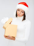 Suspicious woman in santa helper hat with gift box Stock Photos