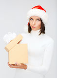 Suspicious woman in santa helper hat with gift box Royalty Free Stock Photo