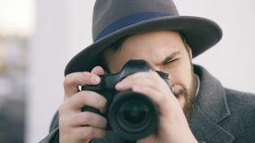 Suspicious young photogpraher man taking picture of you. Concept of hipster male spy agent in hat photographing and. Looking in camera stock video footage