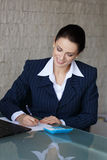 Sussessful businesswoman writing and laughing Royalty Free Stock Photography