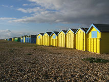 Sussex Beach Huts. Beach huts on Sussex coast in sunshine with storm gathering in background Stock Photos