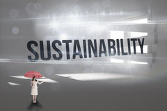 Sustainability against digitally generated room with bordered up window. The word sustainability and attractive businesswoman holding red umbrella against Stock Photo