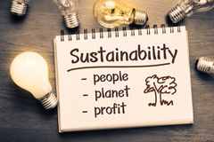 Sustainability. Concept as memo on notebook with light bulbs Royalty Free Stock Photo