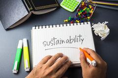 Sustainability. On the desk with handwriting of Sustainability word in notebook Royalty Free Stock Photography