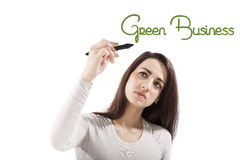 Sustainability. Green business. Sustainability. Beautiful girl presenting and writing the word green business on white board, looking toward the camera Royalty Free Stock Photos