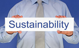 Sustainability sign. An unidentified  businessman wearing a shirt and tie and holding in his hands a white sign with blue text reading sustainability Stock Images