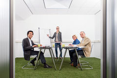 Sustainability strategy meeting. Small business meeting, with four people in a small stylish conference room with grass on the floor, discussing strategy, growth Royalty Free Stock Photo