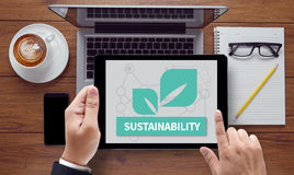 SUSTAINABILITY. On the tablet pc screen held by businessman hands - online, top view Royalty Free Stock Images