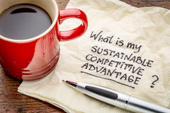 Sustainable competitive advantage concept. What is my sustainable competitive advantage question - handwriting on a napkin with a cup of coffee royalty free stock image