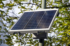 Sustainable solar panel with trees in the background for the environment. Sustainable small solar panel with branches and leaves of trees in the background for royalty free stock image