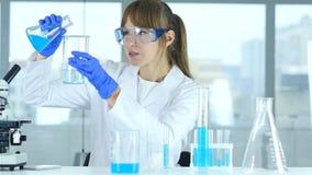 Sustancia química de colada del científico de sexo femenino de la investigación en el cubilete para la reacción en laborato almacen de video
