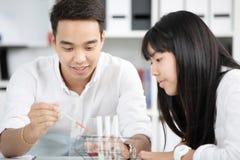 Sustancia química de colada del profesor en el tubo de ensayo con su estudiante Fotos de archivo