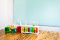 Sustancia química multicolora en el tubo de ensayo de cristal en soporte plástico y el cubilete en la tabla de madera Con el espa fotografía de archivo libre de regalías