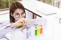 Sustancias de mezcla del estudiante femenino joven del científico en tubo de ensayo imagen de archivo libre de regalías