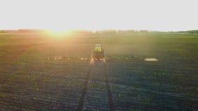 Sustancias químicas de rociadura del tractor en un campo en la puesta del sol metrajes