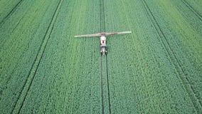 Sustancias químicas de rociadura de la maquinaria agrícola de la visión aérea en el campo verde grande metrajes
