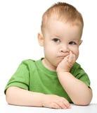 Sustentação pensativa do rapaz pequeno sua cabeça com mão fotografia de stock royalty free