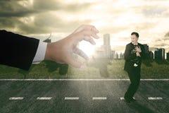 Susto running do homem de negócios que está sendo perseguido por uma mão grande fotografia de stock