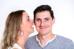 Susurro de la mujer joven en el oído de su novio imagen de archivo