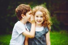 Susurros del niño pequeño y de la muchacha Foto de archivo