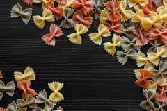 Suszę coloured farfalle makaron na czarnym textured drewnie od above S Obrazy Stock