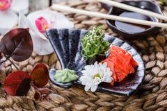 Suszi Gunkan mak z gałęzatką, sezamem i kremowym serem na czarnym talerzu na bambus macie, dekorował z kwiatami Japońska kuchnia Obrazy Stock