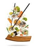 Suszi kawałki umieszczający między chopsticks na białym tle Fotografia Stock