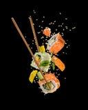 Suszi kawałki umieszczający między chopsticks na czarnym tle Obrazy Royalty Free