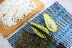 Suszi przygotowanie w kuchni, świeżych składników avocado zielony cięcie w połówce z gałęzatką i biel, gotowaliśmy ryż na drewnia obrazy stock