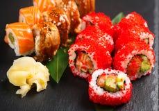 Suszi rolek zbliżenie Japoński jedzenie w restauraci Rolka z łososiem, węgorzem, warzywami i latającej ryba kawiorem, Obrazy Stock