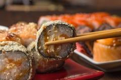 Suszi rolka w tempura z chopsticks na grupie suszi tło Obraz Stock
