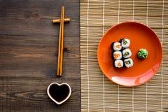 Suszi rolka z łososiem i avocado na talerzu z soja kumberlandem, chopstick, wasabi na drewnianego stołowego tła odgórnym widoku fotografia royalty free