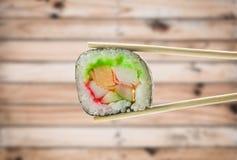 Suszi rolka z chopsticks nad drewnianym tłem Zdjęcia Royalty Free