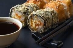 Suszi rolki set w tempura i kijach z soja kumberlandem na czerni Zdjęcie Royalty Free