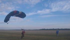 Sutiski, Украина - 24-ое июня 2017: Skydivers носят парашют после приземляться Skydive Украина skydiving центр Стоковые Фотографии RF