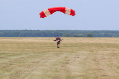Sutiski, Ukraine - June 24, 2017: Skydivers carries a parachute after landing. Skydive Ukraine is the skydiving center. Located at Sutiski Aerodrome, about 20 Stock Image