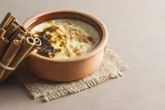 Sutlac turco cocido del postre del pudín de arroz en cazuela de la loza de barro con los palillos de canela fotos de archivo