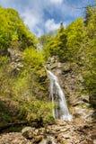 Sutovsky瀑布在春天森林里在蓝天下 库存图片