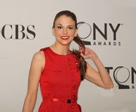 Sutton Foster. Actress Sutton Foster proudly points to her nominee's pin as she arrives for the 65th Annual Tony Awards Meet the Nominees Press Junket at the Royalty Free Stock Image