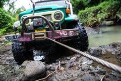 SUV在热带密林- 2013 3月7日,冒险趟过一条岩石河的汽车热心者使用修改过的四轮汽车 库存照片